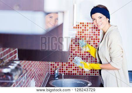 Closeup of a young housewife washing dishes