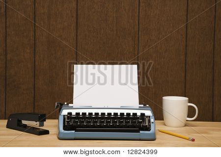 Vintage typewriter, coffee cup, pencil and stapler on desk.