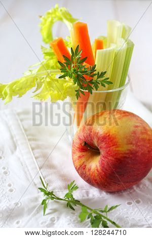 Healthy nutrition: apple, carrot and celery on white table