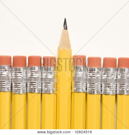 Sharp pencil raised above row of pencils with eraser ends up.