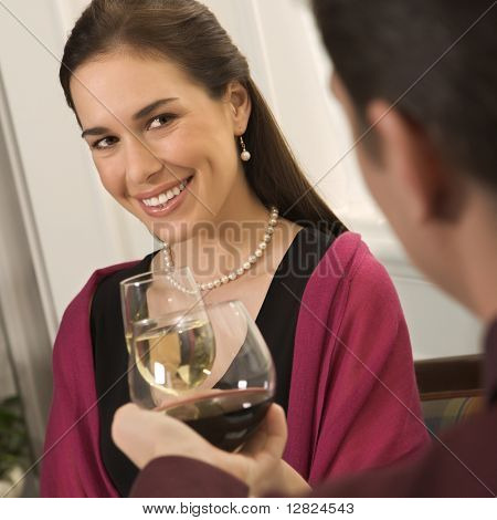Mid adult Caucasian couple smiling and toasting wine glasses.