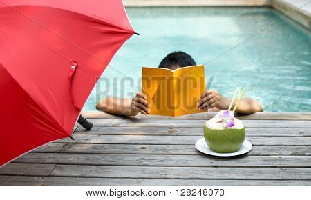 Man relaxing reading a book and having coconut juice with flower by the swimming pool