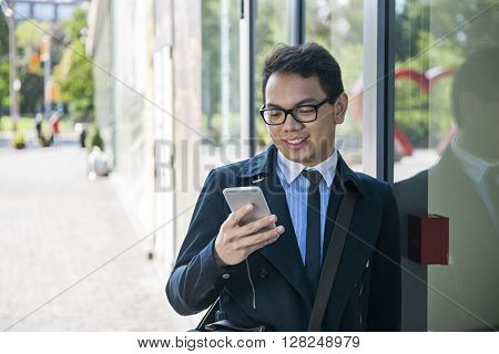Young asian business man looking at mobile phone outside on city street with copy space
