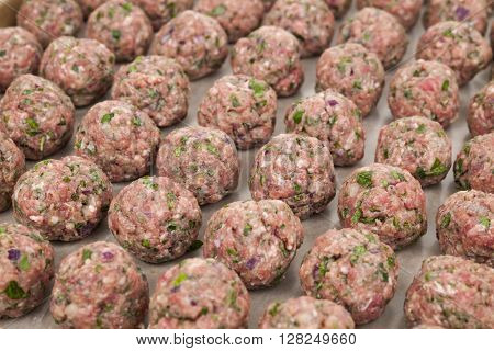 Rows of raw homemade meatballs prepared for cooking on a tray