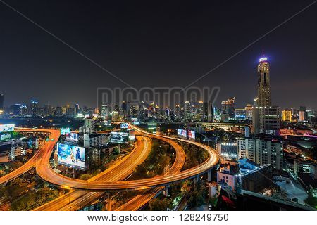 BANGKOK THAILAND - 16 APRIL 2016 - Scene of Bangkok high-rise buildings and traffic light trails on expressway at dusk.