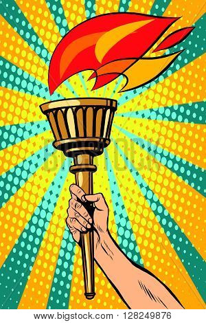 Vector torch with fire in the hand pop art retro style. Ancient antique Holy fire. The sports torch. Political symbol