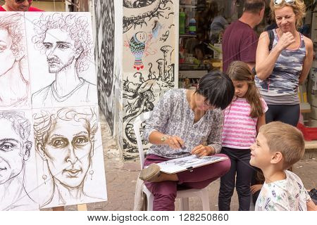 Tel Aviv, Israel - April 28, 2016: Street cartoonist draws a caricature surrounded by people in Tel Aviv, Isarel