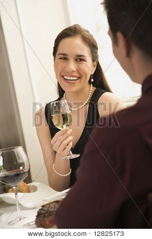 Mid adult Caucasian couple smiling and drinking wine and dining.