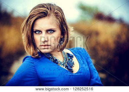 Closeup portrait of young woman in bluea dress