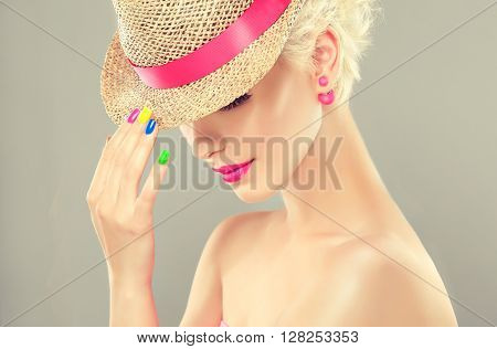 Beautiful girl in a straw hat with colorful makeup and manicure nails . Stylish blonde girl with bright makeup and colorful nail Polish on nails . Spring and summer look and Earrings beads
