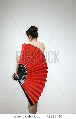 Nude Caucasian woman holding fan covering her back.