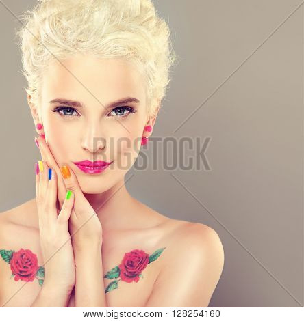 Beautiful model with colorful makeup and nail Polish . Stylish blonde with bright makeup and colored nail Polish .  Blonde with short hair . Spring and summer look woman with earrings  beads and a rose tattoo