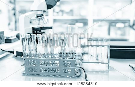 Microscope and test tubes on laboratory bench