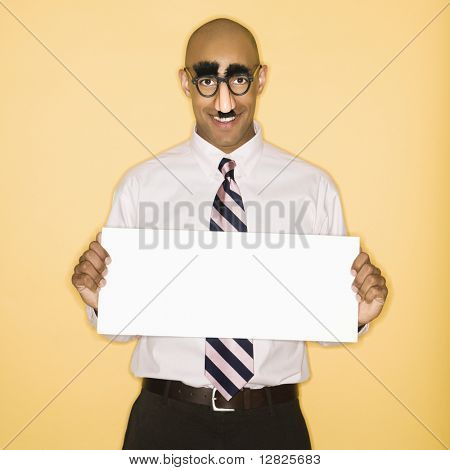 African American man wearing groucho mask disguise holding blank sign.