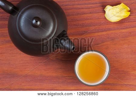 Clay glazed bowl with brewed tea and clay teapot on red wooden table decorated yellow rose petal, top view with place for text