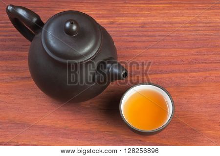Clay glazed bowl with brewed tea and clay teapot on red wooden table with place for text, focused on bowl