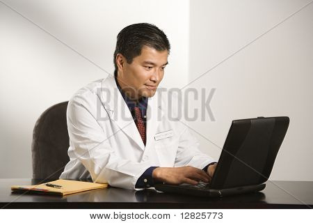 Asian American male doctor sitting at desk with charts typing on  laptop computer.