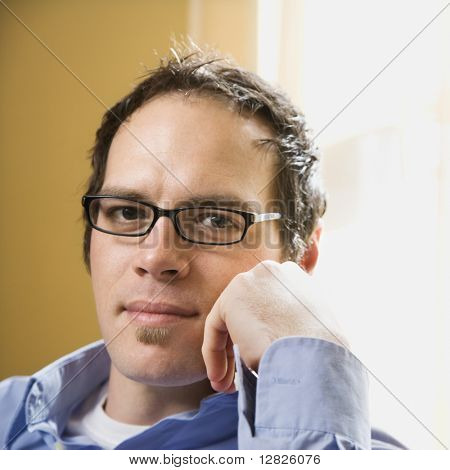 Caucasian mid adult man wearing glasses and looking at viewer with hand to face.