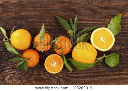 Fresh ripe mandarines with green leaves on wooden table. Organic fresh mandarines healthy fruit eating.