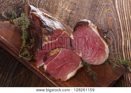 Traditional smoked meat on wooden table. Culinary meat eating.