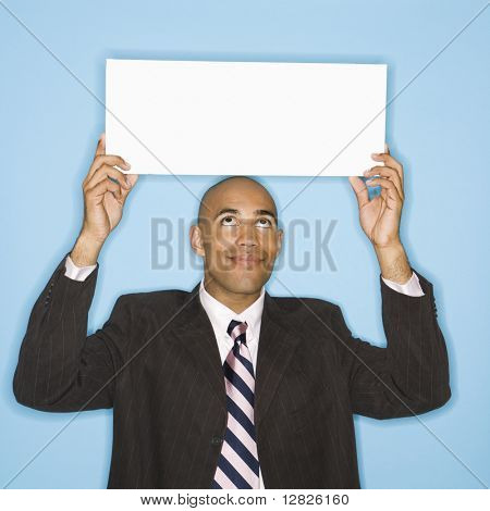 African American man holding blank sign against blue background.