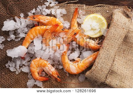 Fresh shrimp with lemon on ice in brown burlap bag on wooden table top view. Culinary seafood eating.