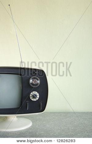 Still life of vintage television set with antenna raised.