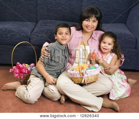 Family sitting on floor with Easter baskets smiling and looking at viewer.