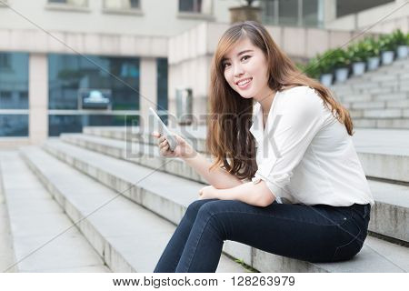 young beautiful asian girl with tablet in school
