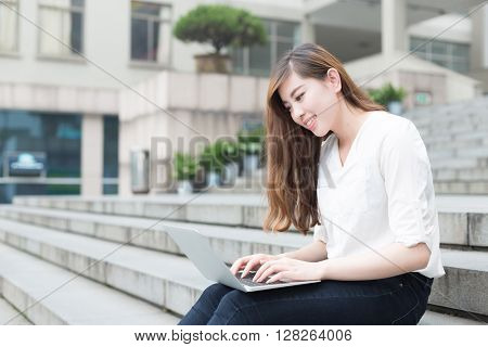 young beautiful asian girl with laptop in school