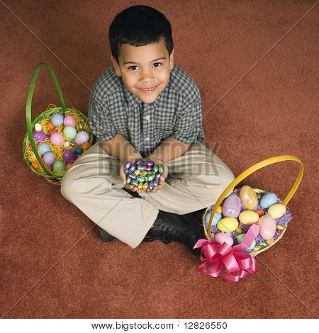 Hispanic boy sitting on floor with two Easter baskets holding chocolate candy eggs in his hands looking up at viewer smiling.