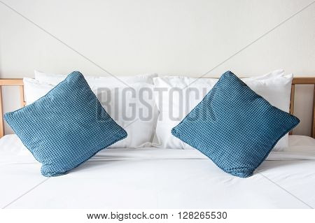 white pillow and blue pillow on bed and with blanket in bedroom