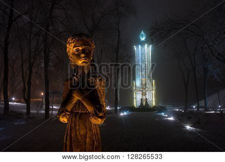 Memorial to Holodomor victims in Kiev (Ukraine). Illuminated girl's sculpture is surrounded with frosted trees. Holodomor (Famine-Genocide ) museum building in background.