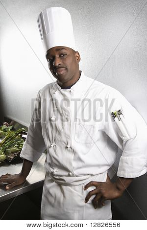 African-American male chef wearing traditional uniform and toque looking at viewer.