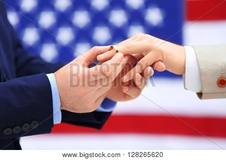 One groom puts ring on another man's finger on American flag background