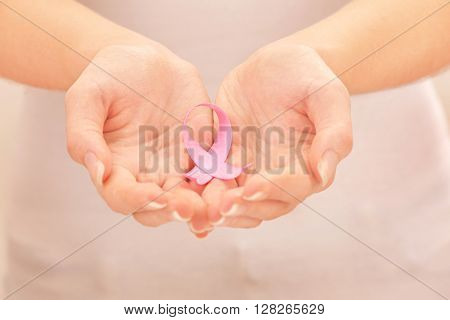 Female hands holding pink ribbon sign, closeup