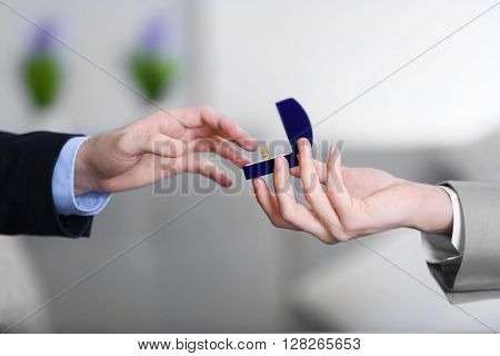 One groom is going to put wedding ring on another man's finger on blurred background
