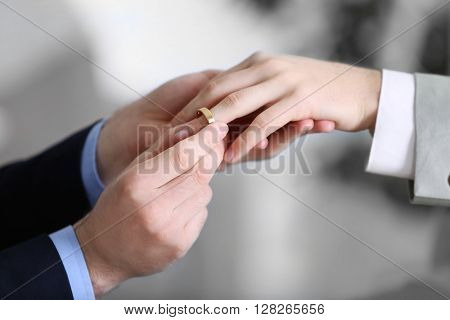 One groom placing the ring on another man's finger
