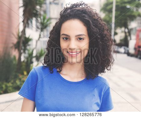 Laughing caribbean woman with blue shirt in vintage warm cinema look