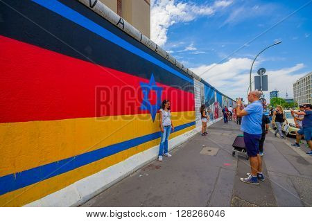 BERLIN, GERMANY - JUNE 06, 2015: Berlin wall full of graffitis and expression of people, turists taking a photo on germany flag colors with Davids star in the middle,