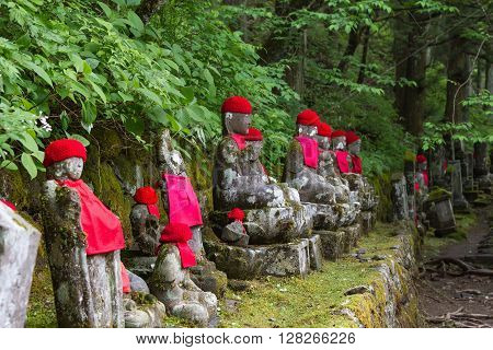 Wide angle view of moss covered statues of Jizo in Nikko, Japan. Front view