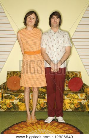 Caucasian mid-adult couple wearing retro clothes standing in room decorated with vintage furniture.