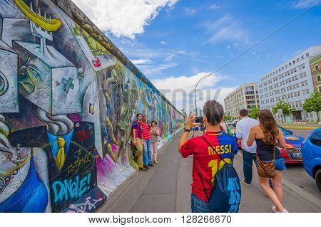 BERLIN, GERMANY - JUNE 06, 2015: Turists taking photographs on graffiti Berlin wall, ways to express theirselves on Berlin