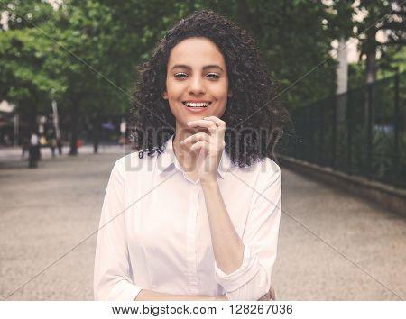 Laughing caribbean woman hair in a park in vintage warm cinema look