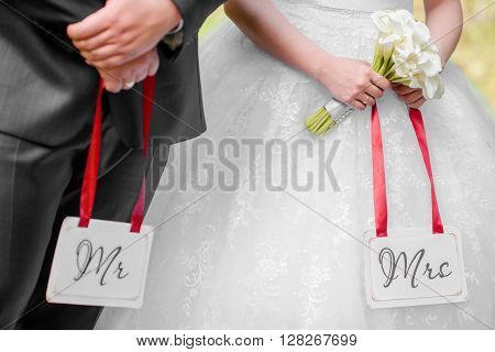bride and groom holding Mr&Mrs labels in their arms