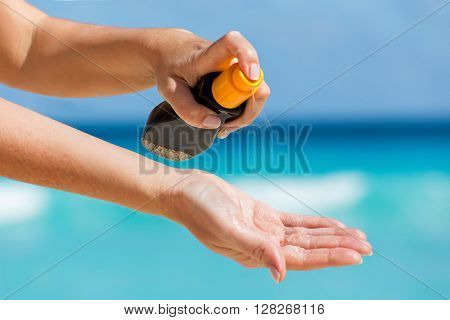Woman Applying Sunscreen Protection Cream Against Turquoise Caribbean Sea Water And Blue Sky