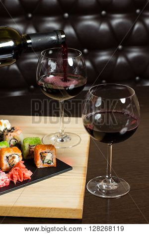sushi colorful mix served dinner with wine glasses on table at restaurant evening date food photography