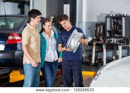 Mechanic Explaining Hubcap To Couple