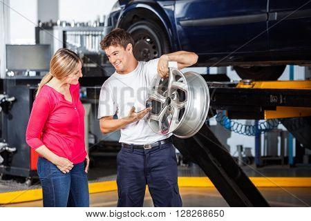 Mechanic Explaining Hubcap To Customer