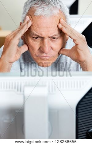 Stressed Senior Man Looking At Computer In Class